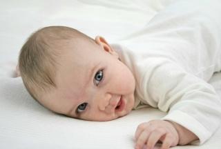 Baby auf Bauch liegend mit offenen Augen
