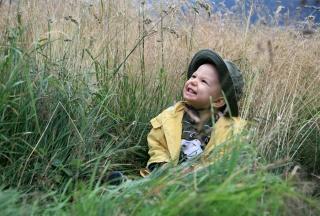 Kind mit Regenschutz im Grünen