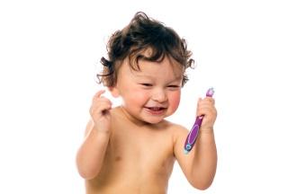 Baby mit Zahnbürste und Schnuller