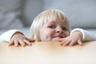 Kleines Kind schaut über den Tischrand