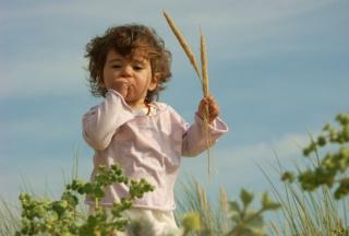 Kleines Kind mit Stöckchen im Grünen