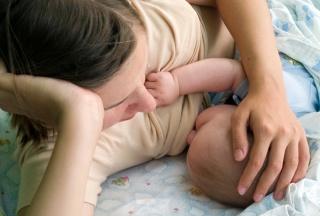 Mutter stillt ihr Baby im Liegen